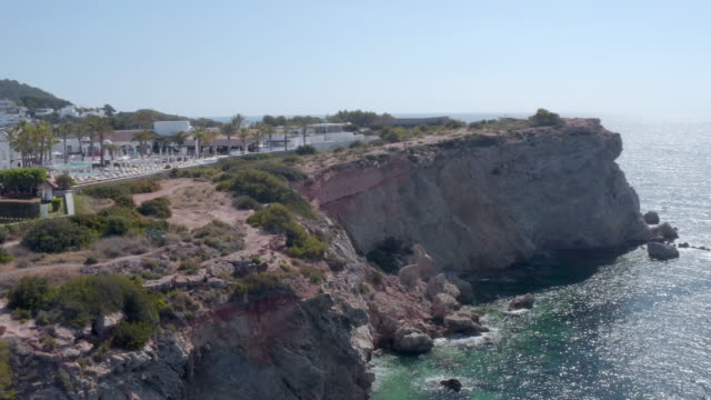 aerial: tourist resort on cliff by sea against sky during sunny day - ibiza, spain - イビサ島点の映像素材/bロール
