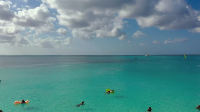 aerial: tourists enjoying beautiful tropical water, some with floats and a couple boats in water away from shore - providenciales, turks and caicos - タークスとケイコス諸島点の映像素材/bロール