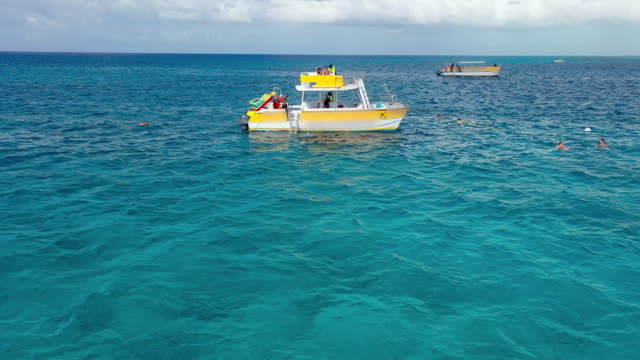 aerial: tourists on yellow pontoon boat and some swimming near boat in tropical water - providenciales, turks and caicos - provo stock videos & royalty-free footage
