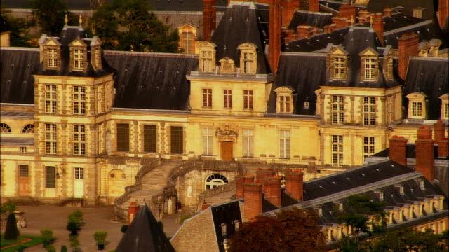 Aerial WS Tourists outside Chateau de Fontainbleau near landscaped gardens / Seine-et-Marne, Ile-de-France, France