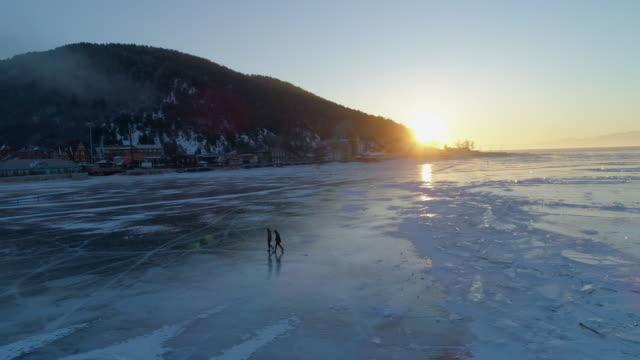 aerial: tourists walking on frozen lake baikal during sunset - frozen stock videos & royalty-free footage