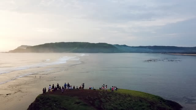 aerial: tourists watching sunset on bali coastline in lombok, bali - bali stock videos & royalty-free footage