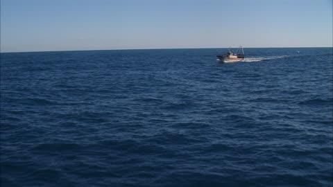 vídeos y material grabado en eventos de stock de aerial towards fishing boat traveling on water - barco pesquero