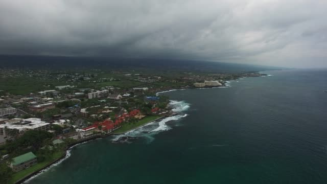 aerial: town by edge of dark ocean on cloudy day - big island hawaii islands stock videos & royalty-free footage