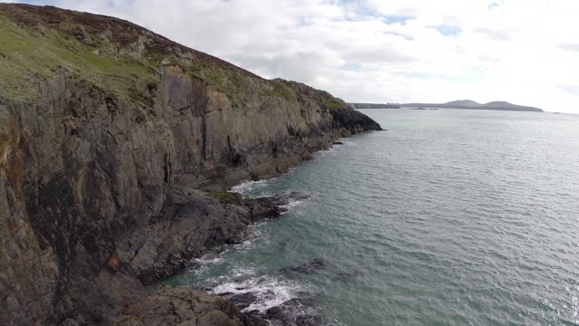 vídeos de stock e filmes b-roll de aerial track along pembrokeshire cliffs with skomer in background - pembrokeshire