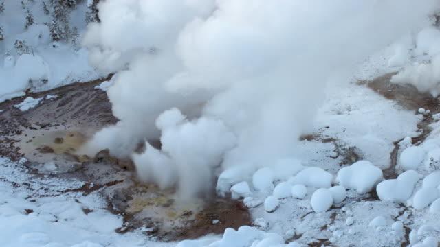aerial track around erupting geyser in winter, yellowstone, usa - geyser stock videos & royalty-free footage