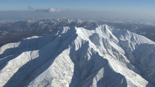 Aerial track around snowy mountain peak. Japan.