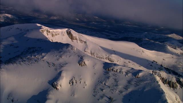 Aerial track away from snowy mountain ridge, Yellowstone, USA