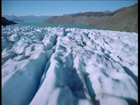 Aerial track down over fissured glacier and out over fjord waters