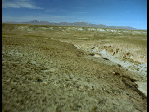 stockvideo's en b-roll-footage met aerial track fast and low over dry bushy scrub, then out over valley on altiplano - ruimte exploratie