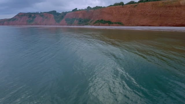 aerial track forward over smooth water to cliff face - sandstone stock videos & royalty-free footage