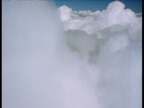 Aerial track high over clouds above rain forest