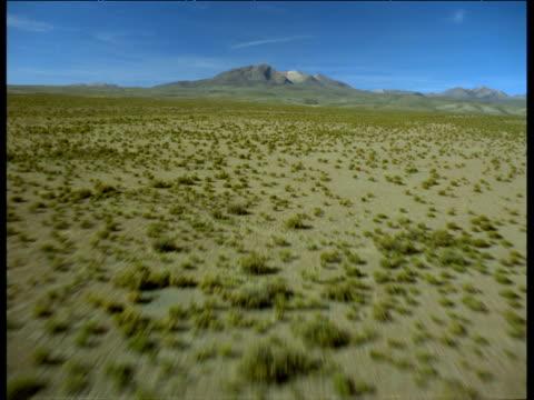 stockvideo's en b-roll-footage met aerial track low over arid scrubland towards distant mountain - ruimte exploratie