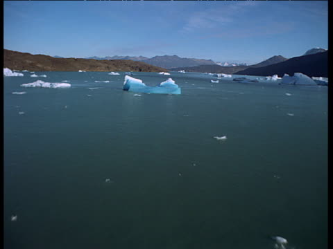 aerial track low over blue iceberg in glacial lake - bbc stock videos and b-roll footage
