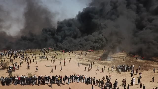 aerial track out of demonstrations at the border between gaza and israel - smoke physical structure stock videos & royalty-free footage