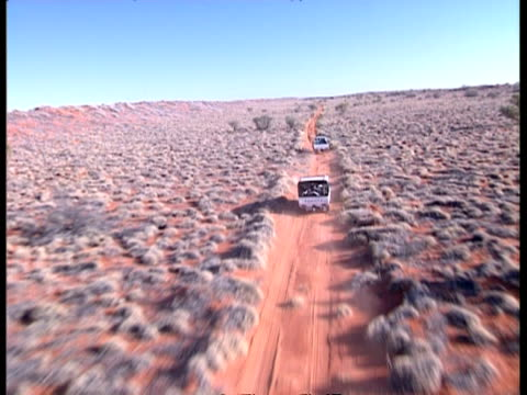 WA Aerial track over 2 4WD's driving down dirt road, Simpson Desert