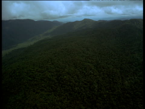 Aerial track over dense cloud forest and slopes