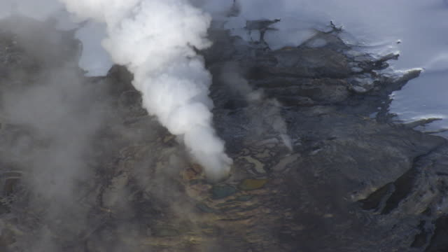 aerial track over erupting geyser in winter, yellowstone, usa - geyser stock videos and b-roll footage