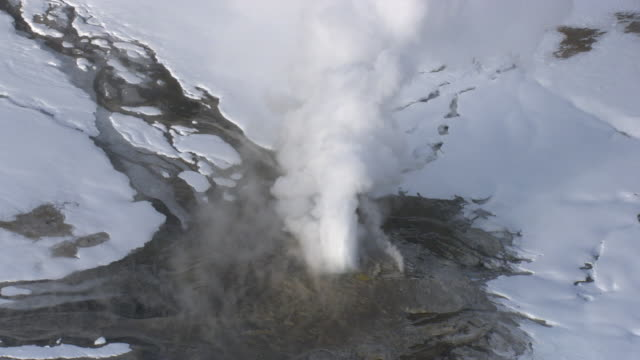 Aerial track over erupting geyser in winter, Yellowstone, USA
