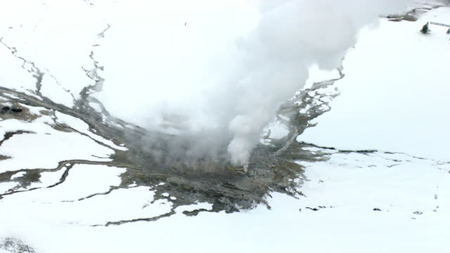 aerial track over erupting old faithful geyser in winter, yellowstone, usa - old faithful stock videos & royalty-free footage