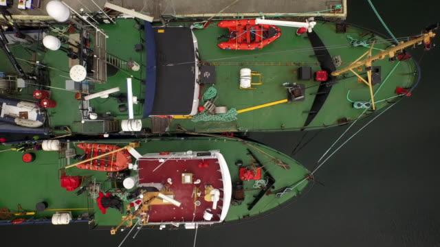 vídeos de stock, filmes e b-roll de aerial track over green decks of moored boats - um do lado do outro