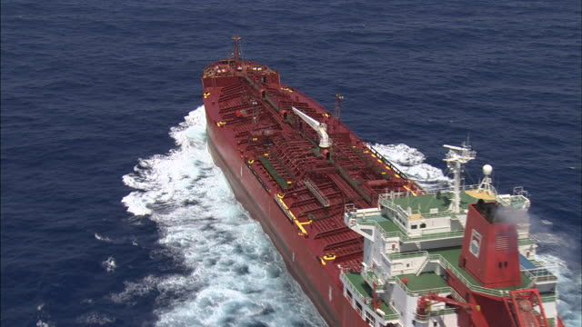 aerial track over huge ship moving through ocean - wake water stock videos & royalty-free footage