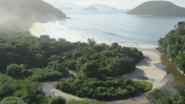 Aerial track over jungle towards coastal islands.