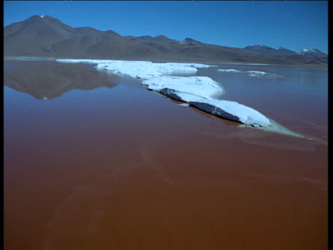 stockvideo's en b-roll-footage met aerial track over large salt islands in middle of brown soda lake - ruimte exploratie