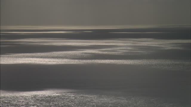 aerial track over light dappled ocean - dappled light stock videos and b-roll footage