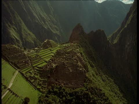 Aerial track over Macchu Picchu Inca ruins, and sun glare
