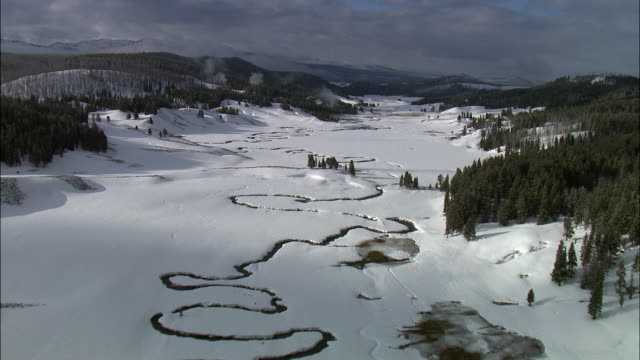 aerial track over meandering river in snowy landscape, yellowstone, usa - yellowstone river stock videos and b-roll footage