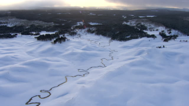 aerial track over meandering river in snowy landscape, yellowstone, usa - river yellowstone stock videos and b-roll footage