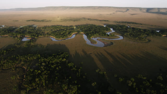 Aerial track over meandering river on savannah at sunset, Kenya