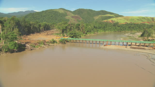 aerial track over meandering river to trucks entering logging area. - papua stock videos and b-roll footage