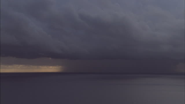 aerial track over ocean with rain in distance and dark storm clouds - ominous stock videos & royalty-free footage
