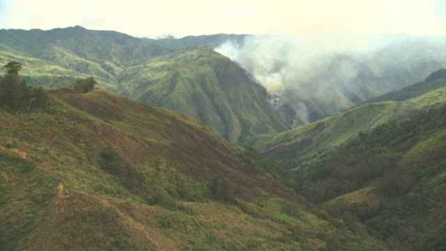 aerial track over ridges towards burning forest on slopes of hill. - papua stock videos and b-roll footage