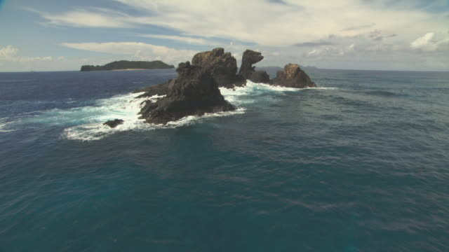 aerial track over rocks jutting from ocean. - pacific ocean stock videos & royalty-free footage