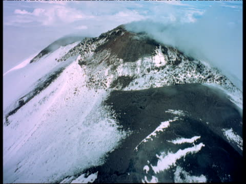 Aerial track over smoking snow covered volcano, some fog on lens