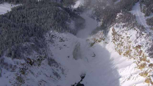 aerial track over snow covered lower falls, yellowstone, usa - river yellowstone stock videos & royalty-free footage