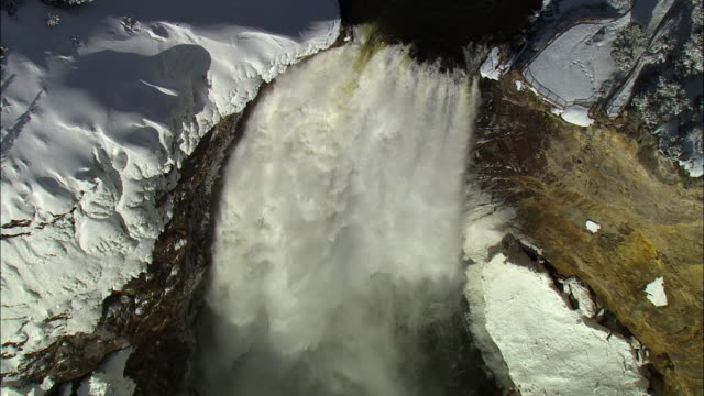 aerial track over snow covered lower yellowstone falls, yellowstone, usa - lower yellowstone falls stock videos & royalty-free footage