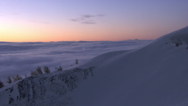 aerial track over snow covered mountain revealing low cloud beyond at sunrise, yellowstone, usa - pink colour stock videos & royalty-free footage