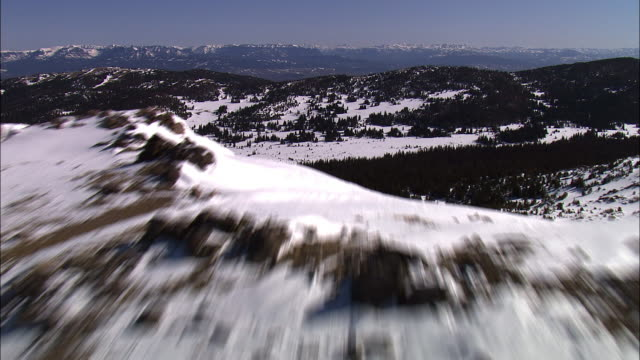 aerial track over snow covered mountain ridge to valley beyond, yellowstone, usa - yellowstone national park stock videos & royalty-free footage