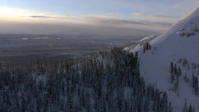 aerial track over snow covered mountain ridge, yellowstone, usa - yellowstone nationalpark stock-videos und b-roll-filmmaterial