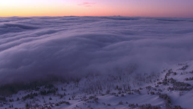 aerial track over snow covered valley and low cloud at sunrise, yellowstone, usa - pink colour stock videos & royalty-free footage
