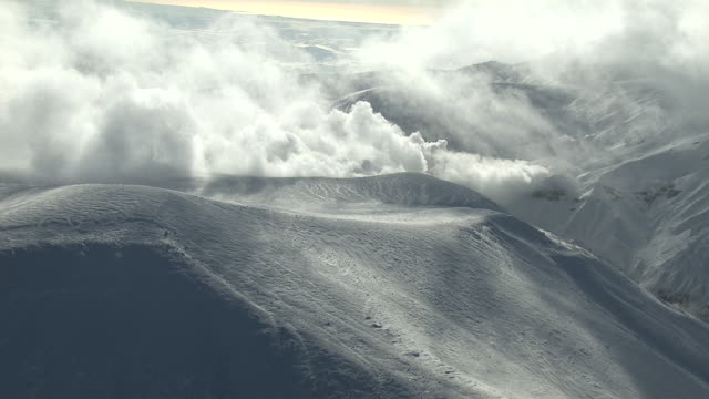 Aerial track over snowy mountain peaks as steam rises from volcanic vents. Japan.