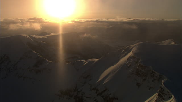 Aerial track over snowy mountains at sunset, Yellowstone, USA