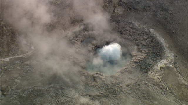 aerial track over steaming and erupting geyser, yellowstone, usa - geyser stock videos and b-roll footage
