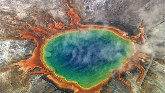 aerial track over steaming grand prismatic spring, yellowstone, usa - cianobatterio video stock e b–roll