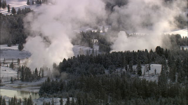 aerial track over steaming hot springs in winter, yellowstone, usa - bbc stock videos and b-roll footage