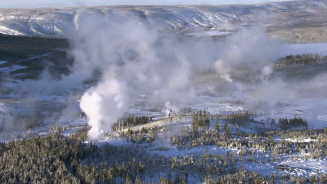 aerial track over steaming hot springs in winter, yellowstone, usa - geyser stock videos & royalty-free footage